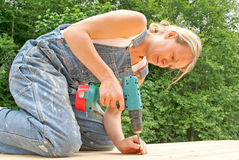 Do it yourself. An attractive woman renovates the deck of her new home stock images