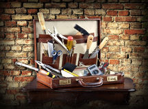 Do it yourself: case full of tools. An assortment of services and maintenance tools in a leather case against a grunge brick background Stock Photos