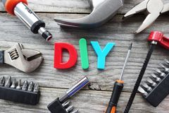 Do it yourself concept with DIY acronym from plastic letters in the middle of tools prepared for work royalty free stock images
