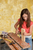 Do it yourself. Girl begins with the renovation of her room. She is using a pliers to remove nails
