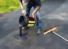 Pouring asphalt sealant on driveway. Do it yourself home maintenance. Driveway resealing repair. Pouring asphalt onto driveway from a bucket royalty free stock photos
