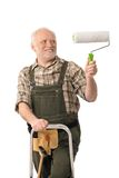 Do it yourself home renovation. Elderly man standing on ladder painting wall Royalty Free Stock Photography