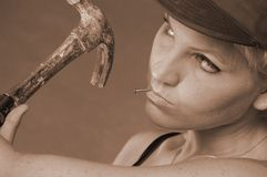 Do-it-yourself kinda girl. Pretty female with nail and hammer in the act of building something sepia toned Royalty Free Stock Images