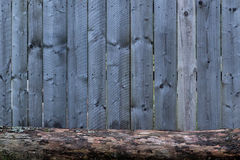 Do it yourself natural wooden fence with a piece of wood in front. Beautiful do it yourself natural wooden  unpainted fence made up from individual pieces Stock Photos