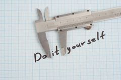 `Do it yourself` - Screw, Nuts and caliper on graph paper. Background Royalty Free Stock Photography