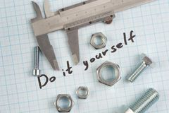 `Do it yourself` - Screw, Nuts and caliper on graph paper. Background Stock Photography
