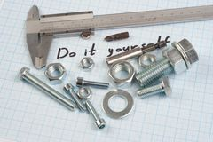 `Do it yourself` - Screw, Nuts and caliper on graph paper. Background Royalty Free Stock Photo