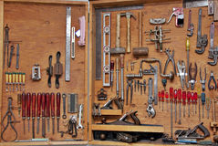 Do it yourself tools. Assortment of diy do it yourself tools hanging in a wooden cupboard against a wall Stock Images