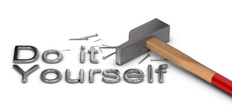 Do it Yourself. Word Do it yourself written with metal letters, one hammer and some nails over white background Royalty Free Stock Images