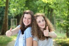 Doação adolescente de dois estudantes polegares acima imagens de stock