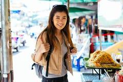 Doação asiática nova da mulher polegares acima do gesto na frente da tenda do alimento da rua foto de stock