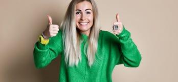 Doação atrativa da jovem mulher polegares acima do gesto da aprovação e do sucesso com um sorriso de irradiação imagens de stock