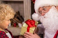 Doação de Santa Claus atual à criança foto de stock royalty free