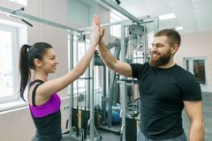 Doação de sorriso nova da mulher da aptidão alta-cinco ao instrutor pessoal Aptidão, esporte, treinamento, pessoa, conceito saudá imagens de stock