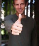 A doação do homem novo os polegares levanta o gesto de mão Foto de Stock