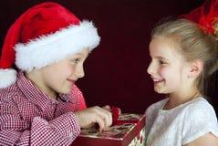 Doação do menino do Natal atual à menina de sorriso foto de stock royalty free