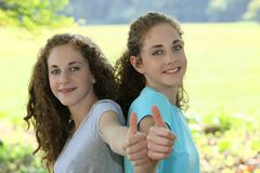 Doação nova de sorriso das irmãs polegares acima imagens de stock royalty free