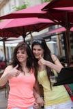 Doação bonita de duas mulheres polegares acima Imagem de Stock Royalty Free