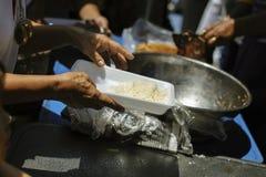 Doar o alimento está ajudando amigos humanos na sociedade: Povos de ajuda com fome com bondade: o conceito de problemas da vida, foto de stock