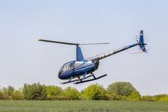 Robinson R44 helicopter flying over grass. DOBANOVCI, SERBIA - AUGUST 26, 2017: Robinson R44 helicopter flying over grass, operated by Balkan Helicopters on Stock Images