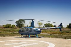 Robinson R44 helicopter parked on helidrom. DOBANOVCI, SERBIA - AUGUST 26, 2017: Robinson R44 helicopter parked on helidrom during World Helicopter Day, operated Stock Images