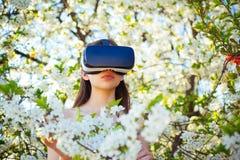 Dobbel och underhållning Faktisk teknologisimulering För klädervr för ung dam exponeringsglas i vårblom Gullig flickalek in arkivbild