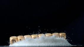 Dobbel spellingsdiabetes die over een stapel van suiker op zwarte achtergrond vallen stock footage