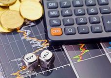 Dobbelt kubussen met de woorden VERKOPEN KOPEN, calculator en gouden muntstukken Stock Foto's