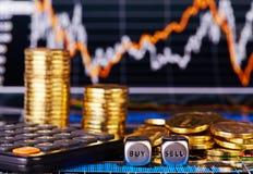 Dobbelt kubussen met de woorden VERKOPEN KOPEN gouden muntstukken, calculator Stock Afbeelding