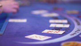Dobbleri Black Jack i en kasino - som är nära upp av att öppna en lek arkivfilmer