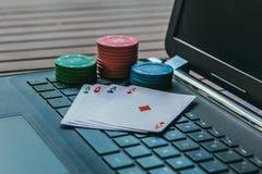 dobbleriböjelsebegrepp Lekpoker som är online- på internet Kort och pokerchiper på en tangentbordbärbar dator royaltyfria bilder