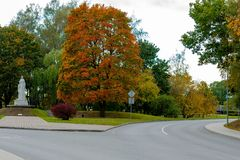 Dobele, Λετονία Τοπίο πόλεων φθινοπώρου με το δρόμο και τους χρωματισμένους σφενδάμνους στοκ φωτογραφία