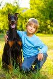 Το αγόρι αγκαλιάζει το αγαπημένο σκυλί του ή doberman το καλοκαίρι Στοκ Εικόνες
