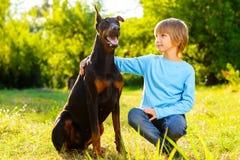 Το αγόρι αγκαλιάζει το αγαπημένο σκυλί του ή doberman το καλοκαίρι Στοκ Φωτογραφία