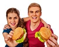 Dobiera się łasowanie fast food Mężczyzna i kobieta jemy hamburger Zdjęcia Stock