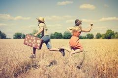 Dobiera się bieg w polu, mężczyzna mienie w jego ręka rocznika walizce na wieś krajobrazu niebieskiego nieba tle outdoors Zdjęcie Stock