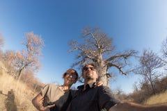 Dobiera się brać selfie blisko baobab rośliny w afrykańskiej sawannie z jasnym niebieskim niebem Fisheye widok spod spodu Pustkow Obrazy Stock