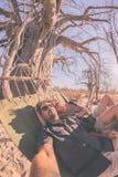 Dobiera się brać selfie na hamaka obwieszeniu od ogromnego baobabu drzewa w afrykańskiej sawannie Fisheye widok, stonowany wizeru Obrazy Stock