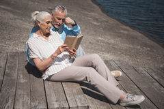Dobiera się czytelniczą książkę podczas gdy odpoczywający na quay przy dniem Obraz Royalty Free
