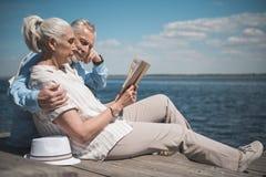 Dobiera się czytelniczą książkę podczas gdy siedzący na quay przy dniem Obrazy Stock