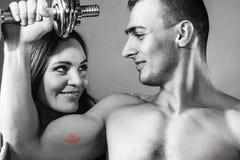 Dobiera się mięśniowego mężczyzna i dziewczyny podziwia jego siłę Obrazy Royalty Free