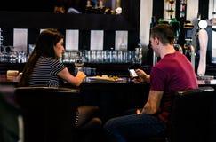 Dobiera się mieć szkło wino podczas gdy mężczyzna texting Obrazy Stock