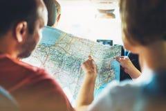 Dobiera się modnisiów przyjaciół patrzeje i wskazuje palec na lokaci nawigaci mapie w auto samochodzie, dwa turystów podróżnika c fotografia stock