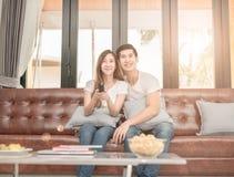 Dobiera się na kanapie z TV dopatrywania daleką telewizją w żywym pokoju obraz royalty free