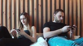 Dobiera się obsiadanie na łóżku, opowiadający each inny, pisać na maszynie na smartphones Młody człowiek i kobieta ma bełt zbiory