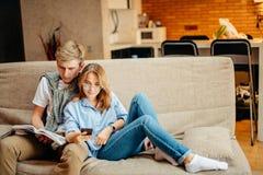 Dobiera się obsiadanie na kanapie, obsługuje czytelniczą książkę, czas wolny wpólnie, kobieta używa telefon zdjęcie stock