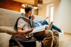 Dobiera się obsiadanie na kanapie, obsługuje czytelniczą książkę, czas wolny wpólnie, kobieta używa telefon obrazy stock