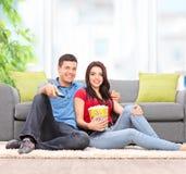 Dobiera się oglądać TV sadzającego na podłoga w domu Zdjęcia Royalty Free