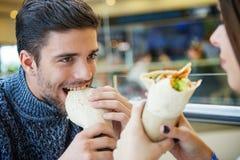 Dobiera się patrzeć each inny podczas gdy jedzący fast food Obrazy Stock