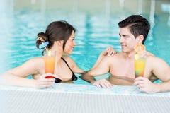 Dobiera się pić koktajl pływackim basenem Zdjęcie Stock